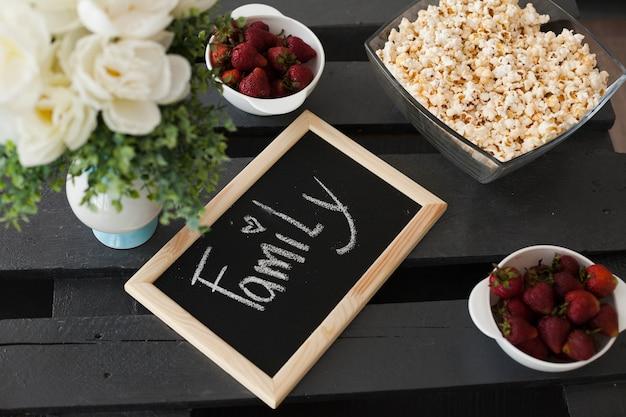 Podwyższony widok truskawka i popkorn z rodzinnym tekstem krytykujemy na drewnianym stole