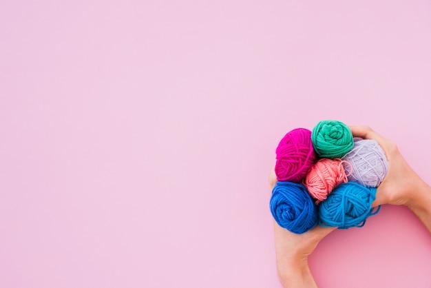 Podwyższony widok trzyma kolorową wełnę na różowym tle ręka