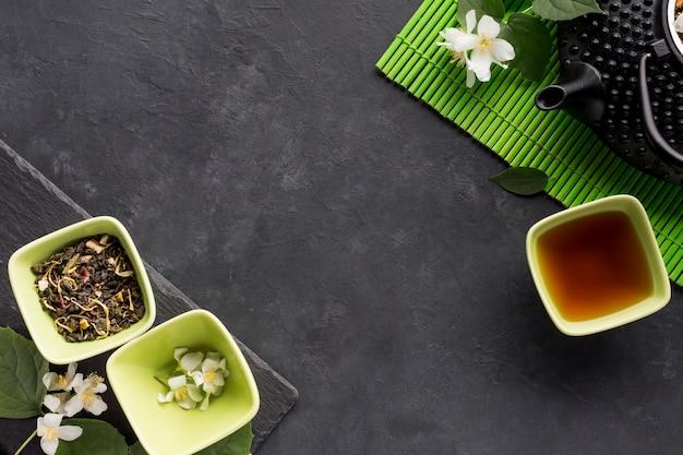 Podwyższony widok wysuszony zielarski składnik z teapot na czerni powierzchni