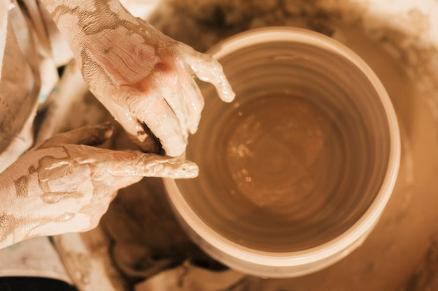 Podwyższony widok żeńska garncarka wręcza robić ceramicznemu garnkowi na ceramicznym kole