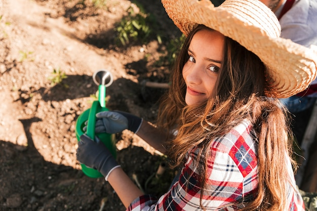 Podwyższony widok żeńska ogrodniczki mienia podlewania puszka patrzeje kamerę