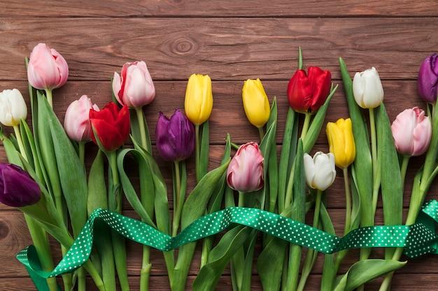 Podwyższony widok zielony faborek nad kolorowymi tulipanami na drewnianej textured desce