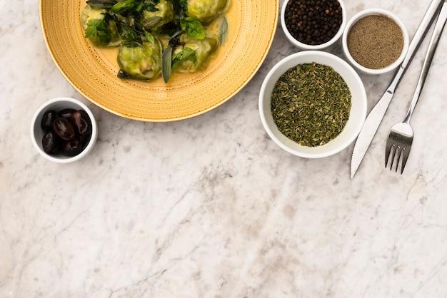 Podwyższony widok zielony pierożek makaron i surowy składnik na marmurze textured tło