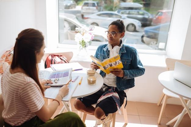 Podyskutujmy. ładna brunetka dziewczyna siedzi w pół pozycji podczas przygotowań do egzaminu