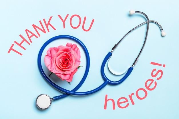 Podziękowania dla bohaterów opieki zdrowotnej plakat pandemiczny covid-19. piękna róża serca i stetoskop na niebieskim tle.