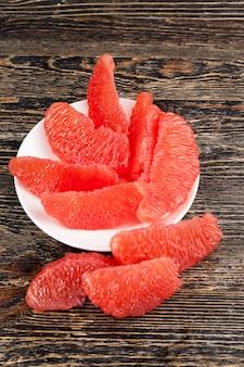 Podzielony na całe plasterki pyszny kwaśny czerwony grejpfrut na stole, czerwone owoce cytrusowe, pyszne zbliżenie grejpfruta