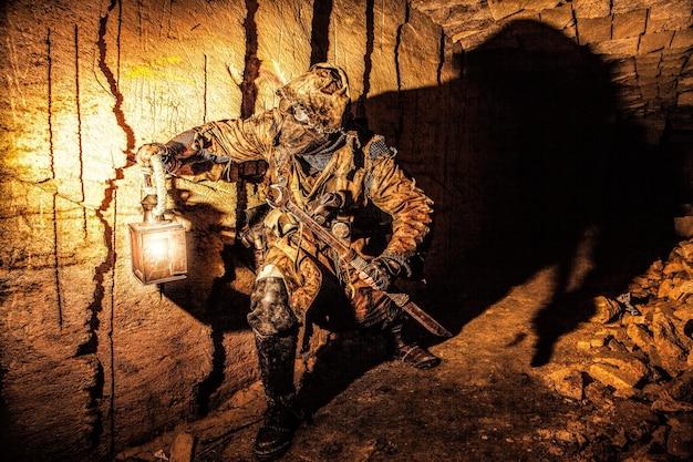 Podziemne postapokaliptyczne stworzenie z bronią i latarnią domowej roboty