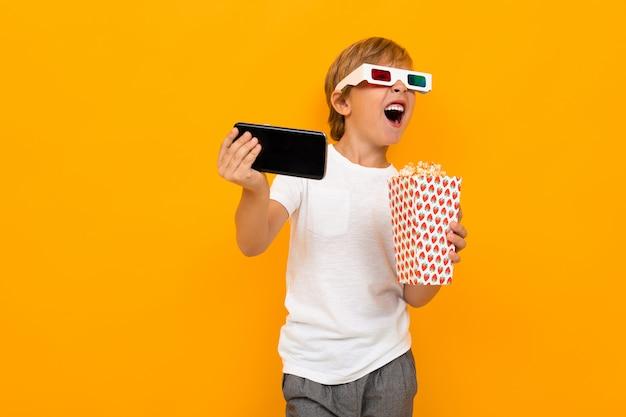 Podziwiający chłopiec w okularach do kina z popcornem i telefonem na żółtej ścianie