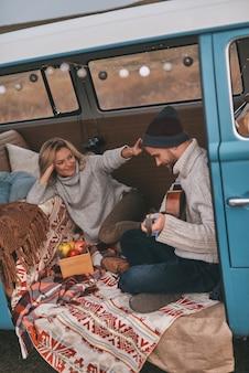Podziwiany przez niego. widok z góry na przystojnego młodego mężczyznę grającego na gitarze dla swojej pięknej dziewczyny, siedząc w niebieskim mini vanie w stylu retro