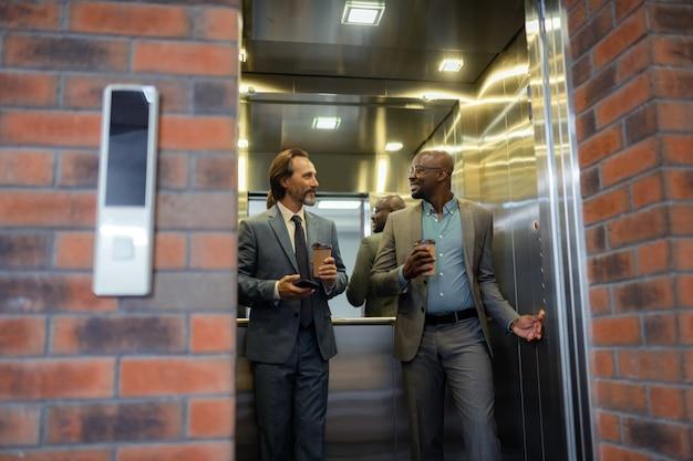 Pogawędka. biznesmen trzymający kawę po krótkiej rozmowie w windzie rano