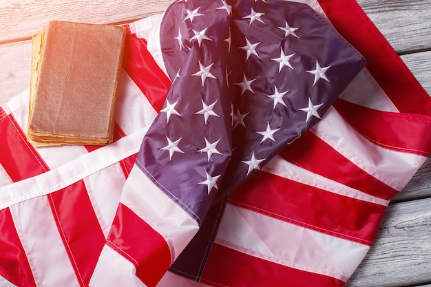 Pognieciona flaga usa i książka. baner i książka w świetle słonecznym. przestrzegaj prawa. prawa człowieka przede wszystkim.