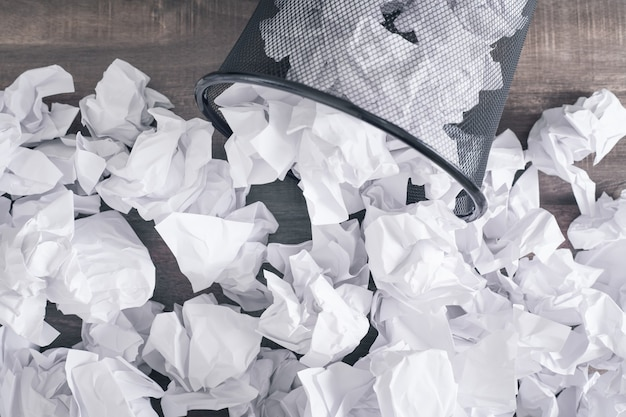 Pogniecione papiery w koszu na śmieci.