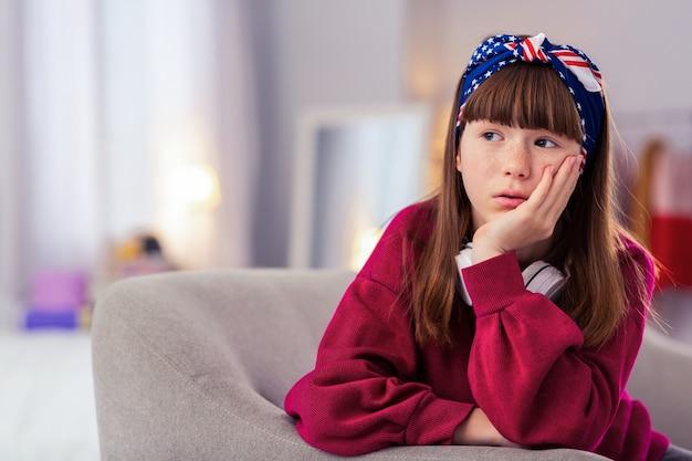 Pogrążony w myślach. ładna dziewczyna, opierając się na kanapie, patrząc na bok