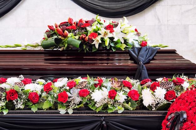 Pogrzeb, pięknie ozdobiony trumną z kompozycjami kwiatowymi, zbliżenie