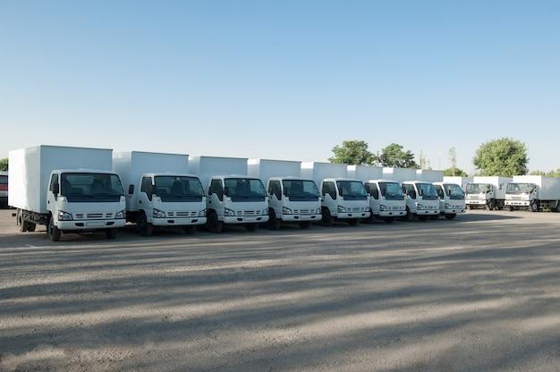 Pojazdy towarowe stoją w rzędzie na parkingu. transport towarowy. parking dla ciężarówek