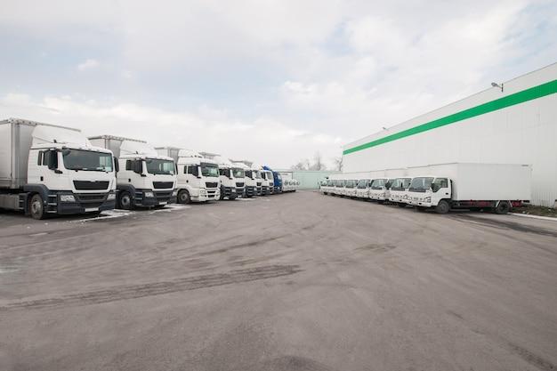 Pojazdy towarowe stoją w rzędzie na parkingu w pobliżu magazynu fabrycznego ciężarówka w magazynie