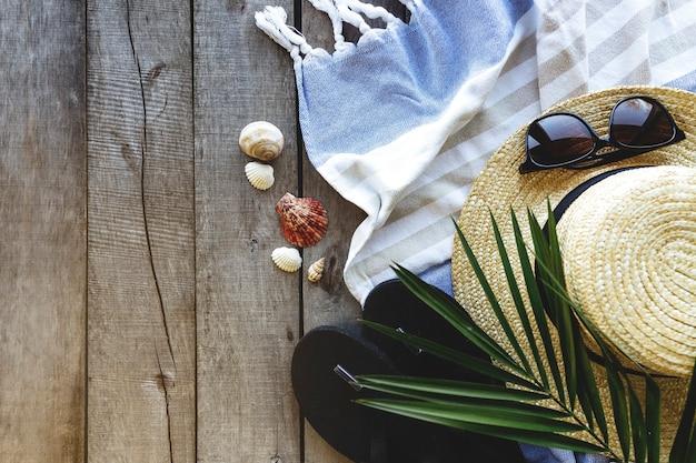Pojęcie aktywności w podróży, na wakacjach lub w weekendy. słomkowy kapelusz z liściem palmowym, buty i okulary, ręcznik na drewnianym stole. czas relaksu