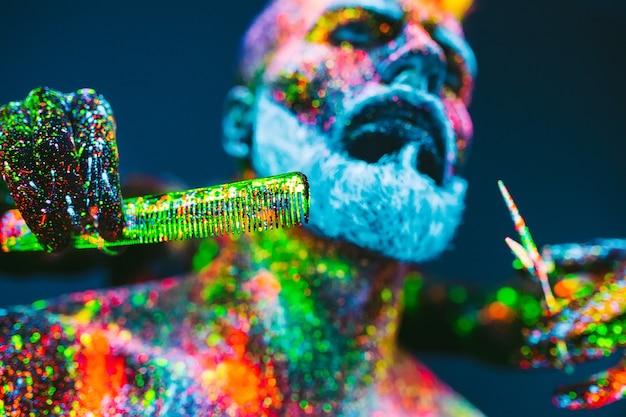 Pojęcie. brodaty mężczyzna w zakładzie fryzjerskim. stylowy brodaty mężczyzna jest obszyty w sklepie fryzjerskim. mężczyzna jest ozdobiony proszkiem ultrafioletowym.