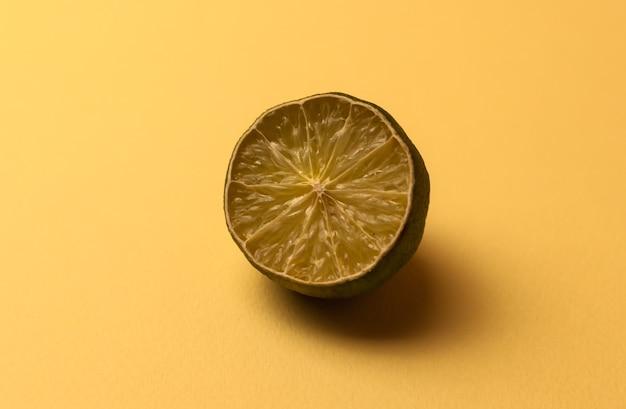 Pojęcie brzydkich owoców i owoców cytrusowych. połowa pokrojonego w plasterki limonki wyschła, zepsuła się