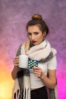 Pojęcie choroby. kobieta z ciepłym kocem i filiżanką gorącej herbaty pozuje z bardzo smutnymi emocjami