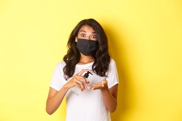 Pojęcie covid-19, dystansu społecznego i stylu życia. obraz afro-amerykańskiej dziewczyny w masce na twarz przy użyciu środka dezynfekującego do rąk, stojąc na żółtym tle.