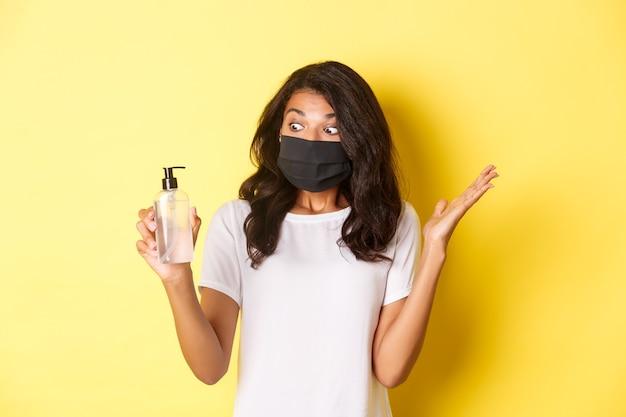 Pojęcie covid-19, dystansu społecznego i stylu życia. obraz zdziwionej afroamerykańskiej dziewczyny, noszącej maskę na twarz, patrzącej na podekscytowany środek do dezynfekcji rąk, stojącej na żółtym tle