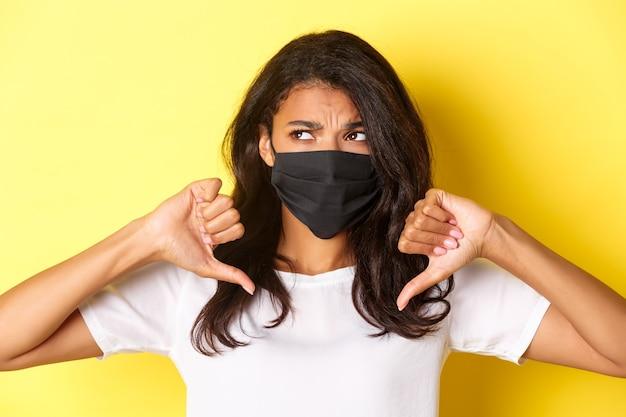 Pojęcie covid-19, dystansu społecznego i stylu życia. zbliżenie na niechętną i niezadowoloną afroamerykankę, ubraną w czarną maskę, pokazującą kciuk w dół i marszczącą brwi.