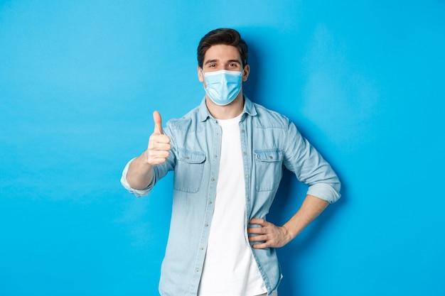 Pojęcie covid-19, pandemii i dystansu społecznego. zadowolony facet w masce medycznej pokazując kciuk do góry z aprobatą, stojący na niebieskim tle