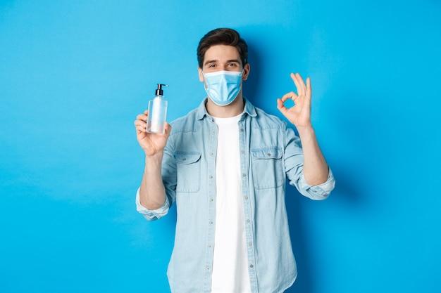 Pojęcie covid-19, pandemii i dystansu społecznego. zadowolony młody człowiek w masce medycznej zalecający środek do dezynfekcji rąk, pokazujący znak ok i środek antyseptyczny, stojący na niebieskim tle