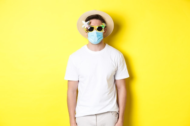 Pojęcie covid-19, wakacji i dystansu społecznego. mężczyzna turysta noszący maskę medyczną i letni kapelusz z okularami przeciwsłonecznymi, wyruszający w podróż podczas pandemii, żółte tło