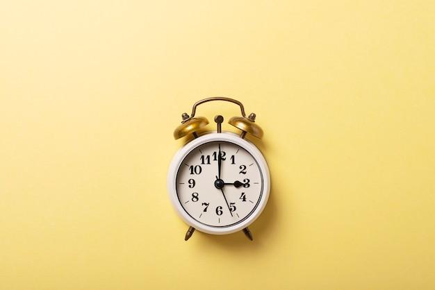 Pojęcie czasu letniego. retro zegar na żółtym tle. widok z góry na dół z miejscem na kopię