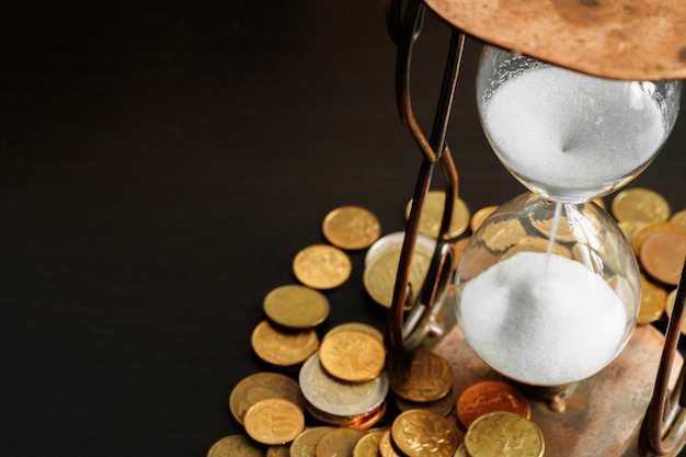 Pojęcie czasu to pieniądz. zamyka up klepsydra z pieniądze monetami