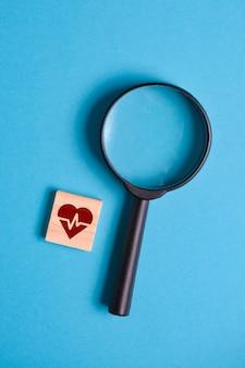 Pojęcie diagnozy serca. znak na drewnianym kwadracie obok lupy