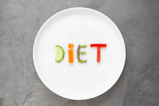 Pojęcie diety. biały talerz ze słowem - dieta - składa się z plasterków różnych owoców i warzyw.