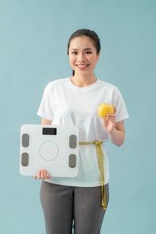 Pojęcie diety i fitness - piękna sportowa kobieta ze skalą, żółtym jabłkiem i miarką