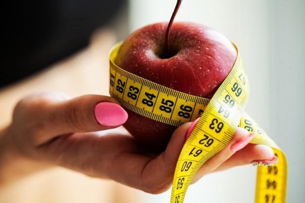 Pojęcie diety. jabłko z miarą taśmy w kobiecej dłoni