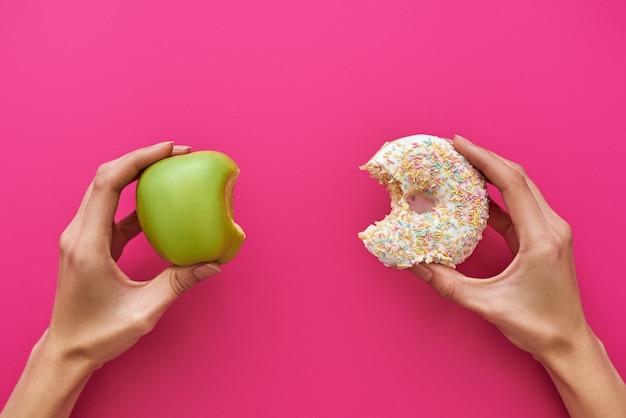 Pojęcie diety lub dobrego zdrowia. młoda kobieta odrzuca niezdrowe jedzenie lub niezdrowe jedzenie, takie jak pączek lub deser, i wybiera zdrową żywność, taką jak świeże owoce lub warzywa.