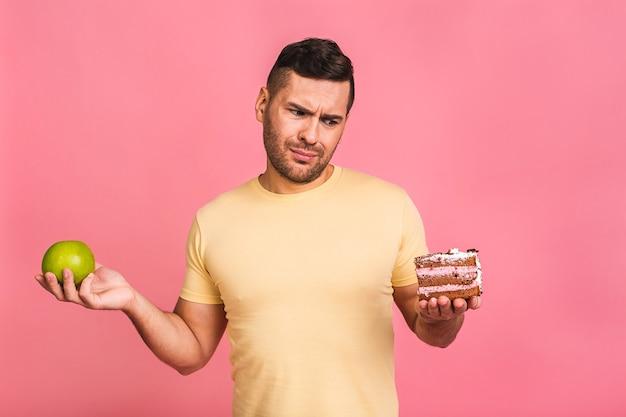 Pojęcie diety. młody człowiek myśli, co jeść między jabłkiem a ciastem