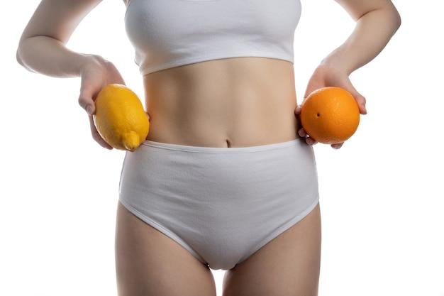 Pojęcie diety, piękny brzuch i owoce na białym tle na białej powierzchni