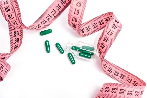 Pojęcie diety. pigułki diety, zielone kapsułki z różową taśmą pomiarową na białym tle