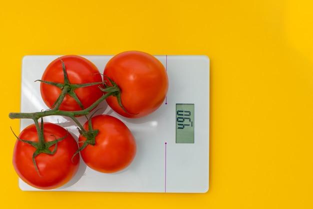 Pojęcie diety, prawidłowego odżywiania, zdrowego odżywiania. świeże pomidory na gałęzi na wadze kuchennej. widok z góry, miejsce kopiowania, układ