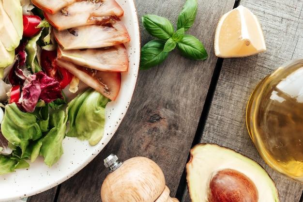 Pojęcie diety śródziemnomorskiej. talerz z liśćmi sałaty, połówka awokado z pestkami
