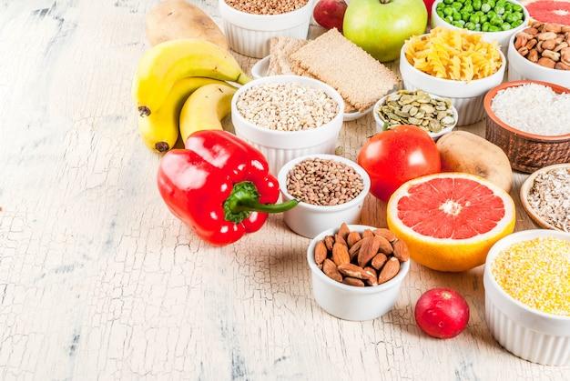 Pojęcie diety tło żywności, zdrowe produkty węglowodanów (węglowodanów) - owoce, warzywa, zboża, orzechy, fasola, jasnym tle betonowym powyżej miejsca kopiowania