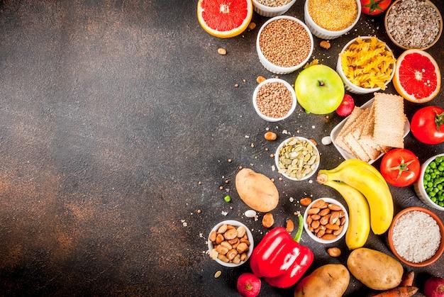 Pojęcie diety tło żywności, zdrowe węglowodany (węglowodany) - owoce, warzywa, zboża, orzechy, fasola, ciemnoniebieskie tło betonu widok z góry kopia przestrzeń