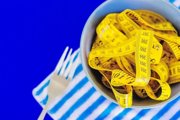Pojęcie diety. widelec przewinął centymetr leżący na talerzu