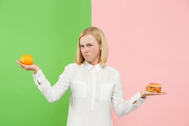 Pojęcie diety. zdrowa żywność. piękna młoda kobieta wybiera między owocami i niezdrowym fast foodem w studio. ludzkie emocje i porównania