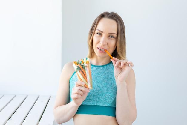 Pojęcie diety - zdrowego stylu życia kobieta jedzenie warzyw uśmiechający się zadowolony pomieszczeniu. młoda kobieta zdrowe jedzenie.