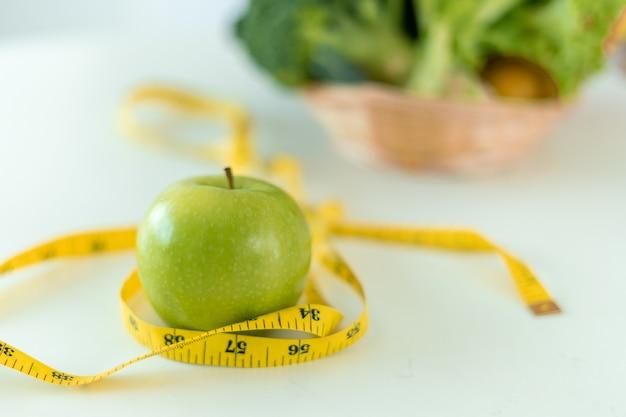 Pojęcie diety. zielone jabłka i centymetrem z odważną sałatką na stole. spożywanie pokarmów bogatych w witaminy dla zdrowia i utraty wagi.