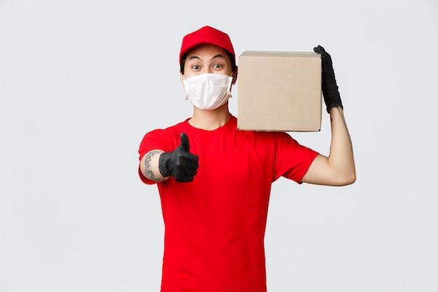 Pojęcie dostawy i nosicieli podczas pandemii koronawirusa. bardzo szybka i dobra usługa dostawy. przyjazny azjatycki kurier pokazujący kciuk w górę, pakiet pudełka na ramię, gwarantujący jakość transferu