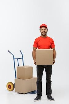 Pojęcie dostawy - portret przystojny mężczyzna afroamerykanów dostawy lub kurierem pchania samochodu ciężarowego z stosu pudeł. pojedynczo na tle szarym studio. skopiuj miejsce.